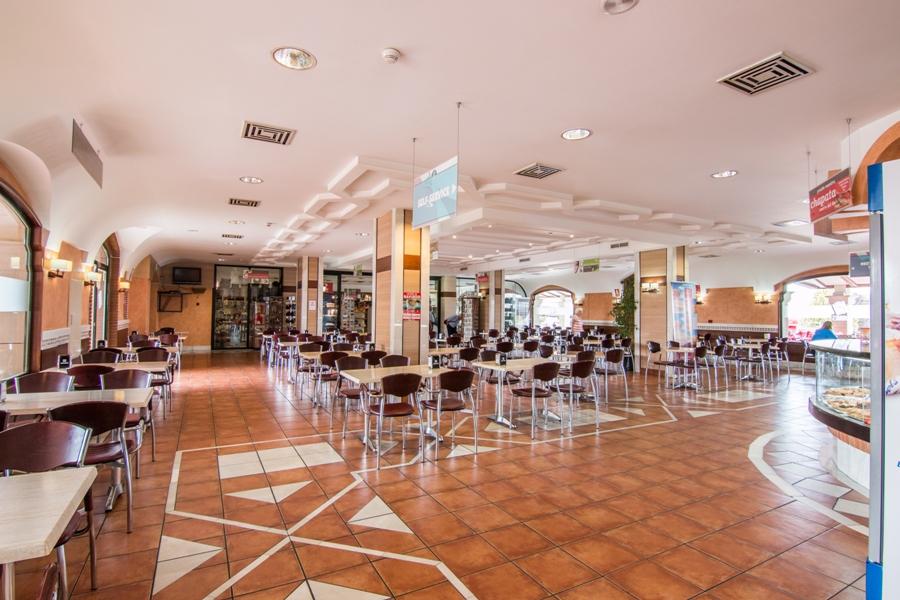 Zona de mesas en la cafetería de Abades Guadix